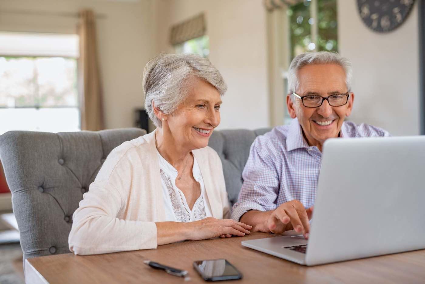 matrimonio de personas mayores usando ordenador felices
